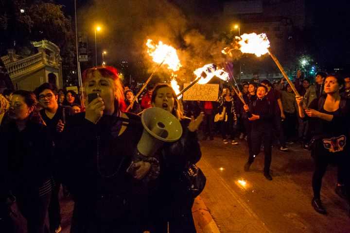 Women carrying torches during a march in Santiago, Chile to protest against femicide and gender violence.