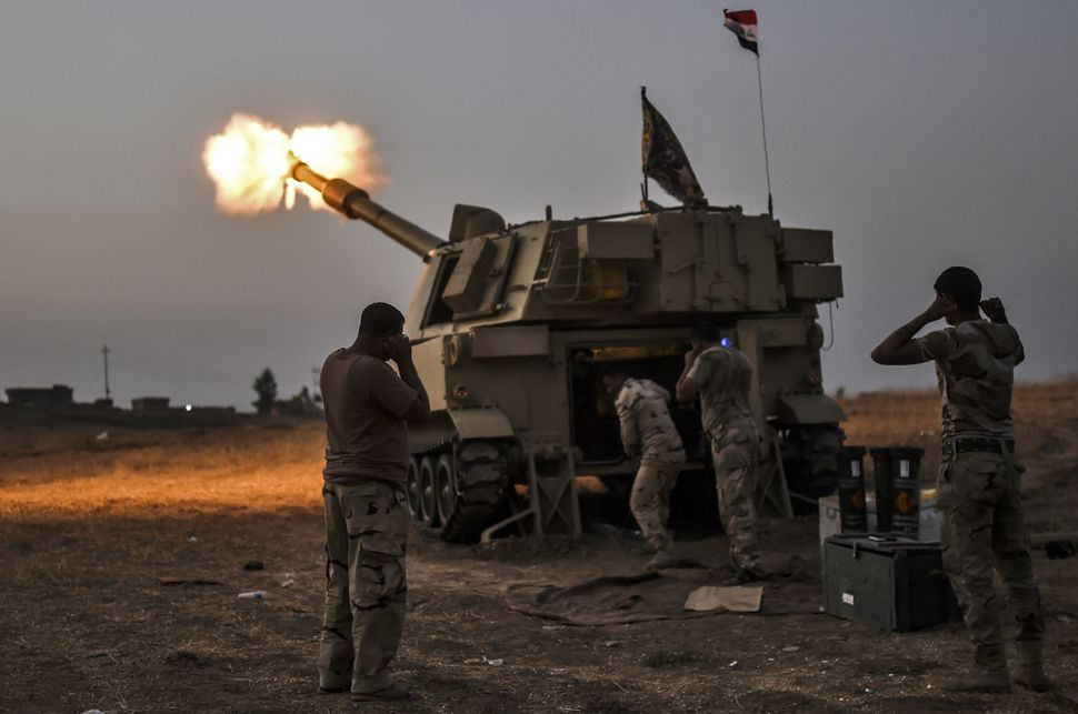 Iraqi forces fire a M109 self-propelled howitzer toward the village of Al-Muftuya from a position in Kani al-Harami, some 21