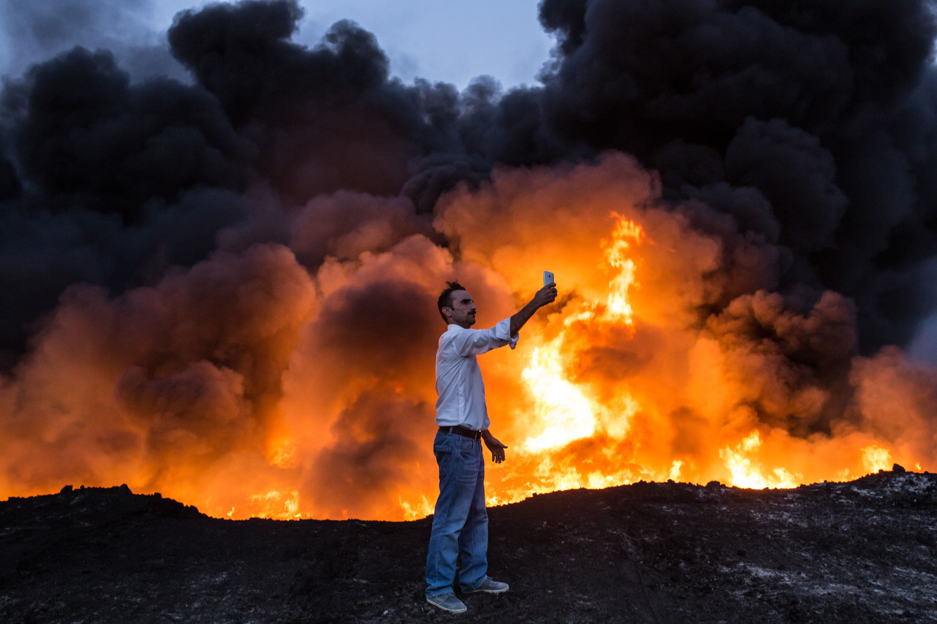 A man takes a selfie in front of oil that has been set ablaze in the Qayyarah area of Iraq, some 35 miles south of Mosul,&nbs