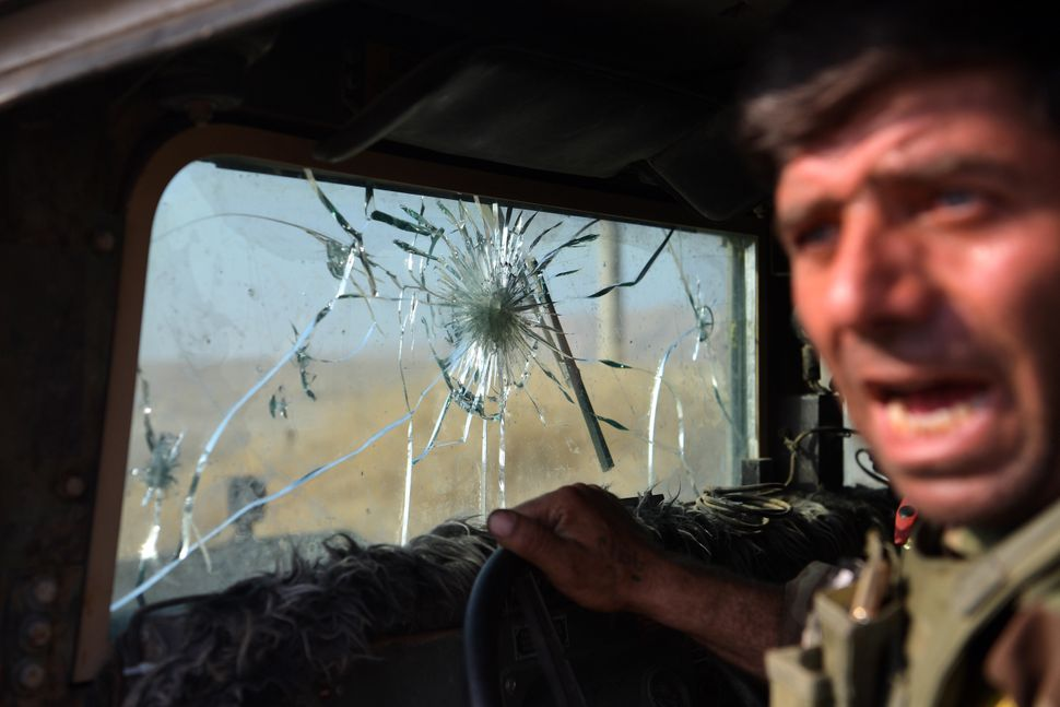 A Kurdish Peshmerga fighter leans out of his military vehicle, which has taken several direct hits from ISIS snipers in the s
