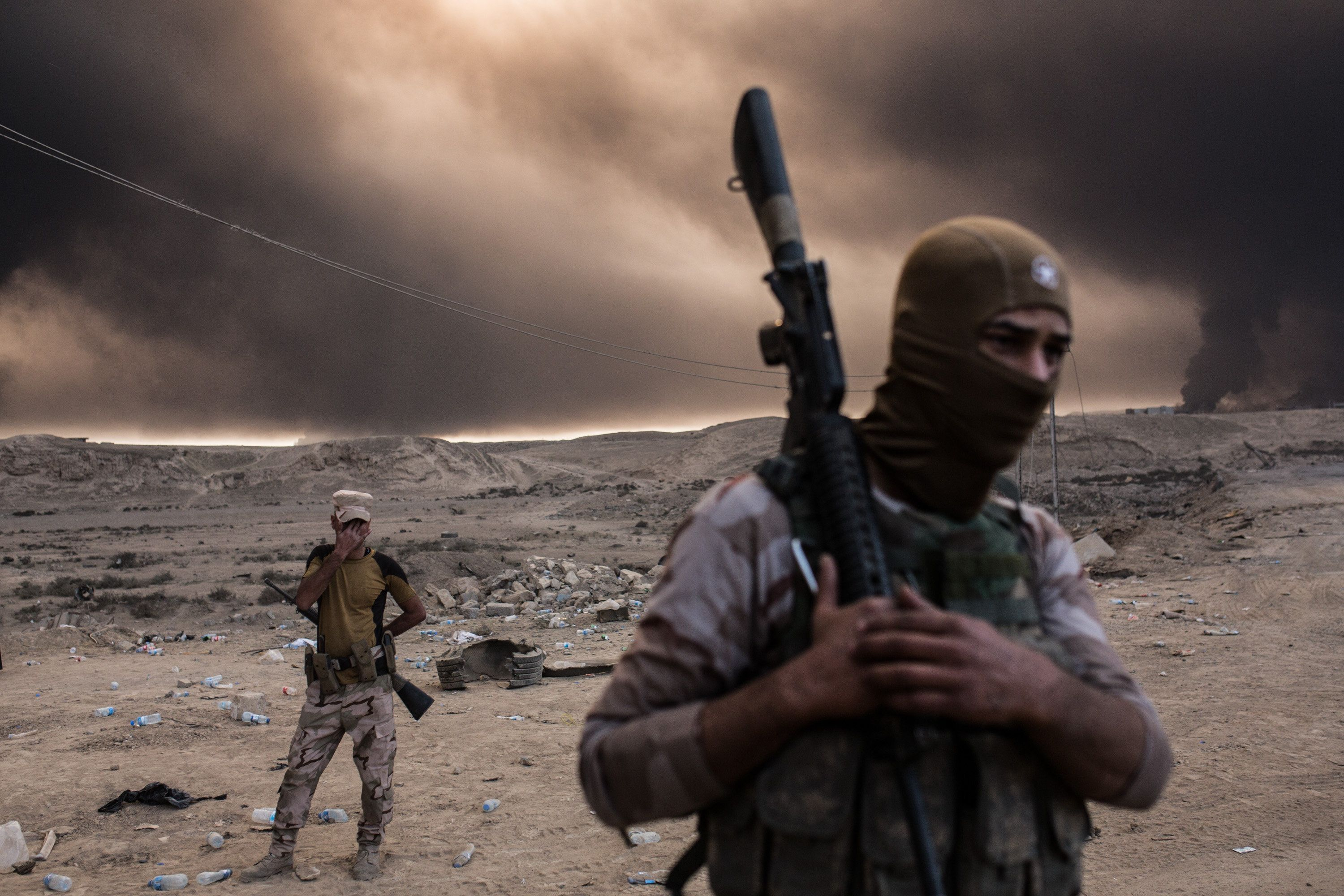 Iraqi soldiers look on as smoke rises from the Qayyarah area, some 35 miles south of Mosul, Iraq, on Oct. 19, 2016.