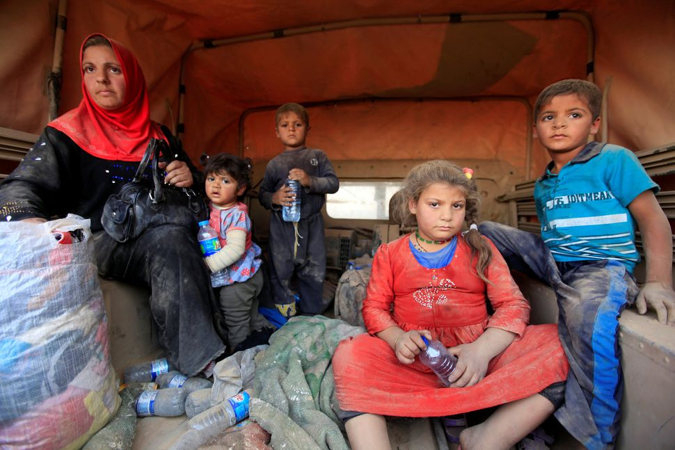 Displaced people who are fleeing from clashes sit inside a military vehicle in Qayyarah while an operation takes place t
