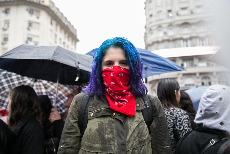 A woman protests in the rain in Buenos Aires.