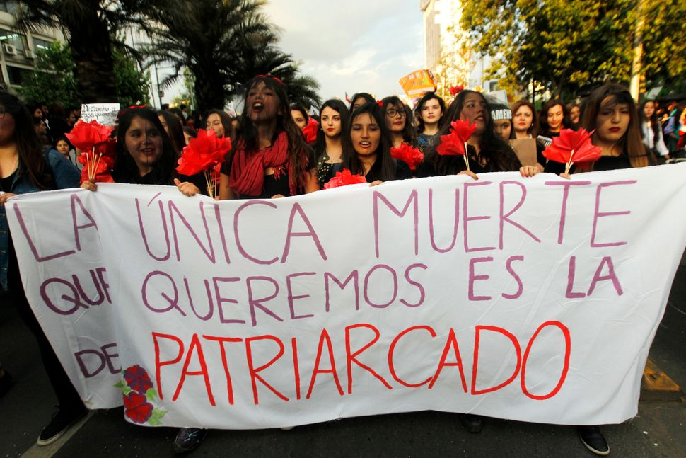 "Women take part in a march in Santiago on October 19 with a sign that says, ""The one death that we want is that of patriarchy"