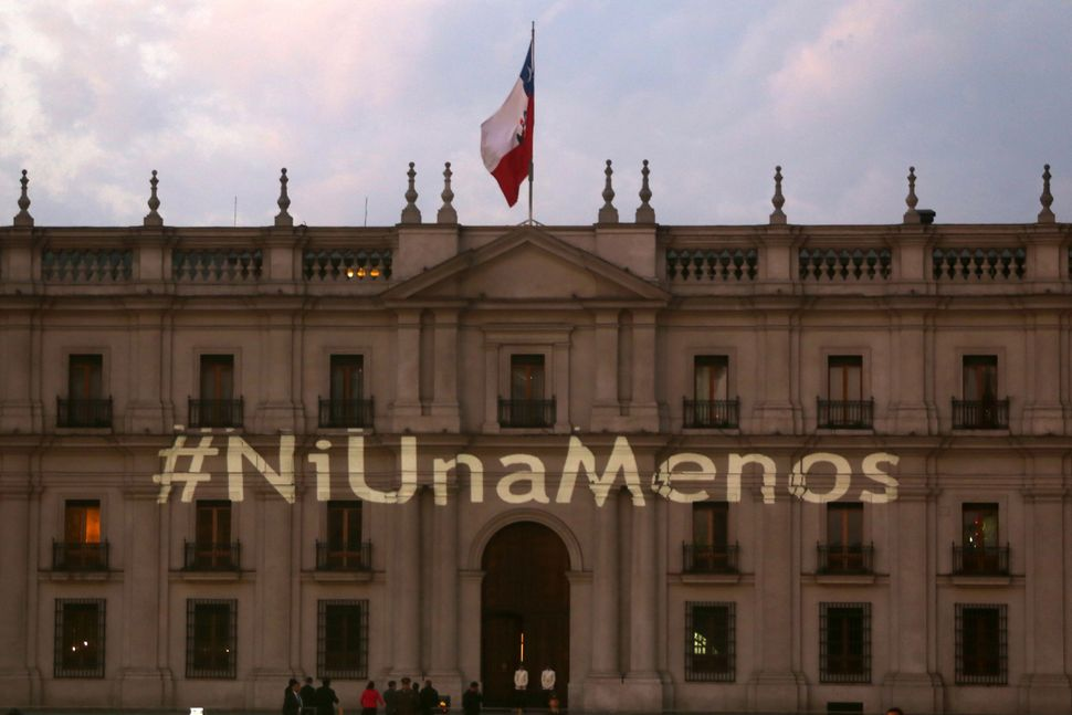 The #NiUnaMenos hashtag is shown on the presidential palace 'La Moneda' during protests in Santiago, Chile on October 19.