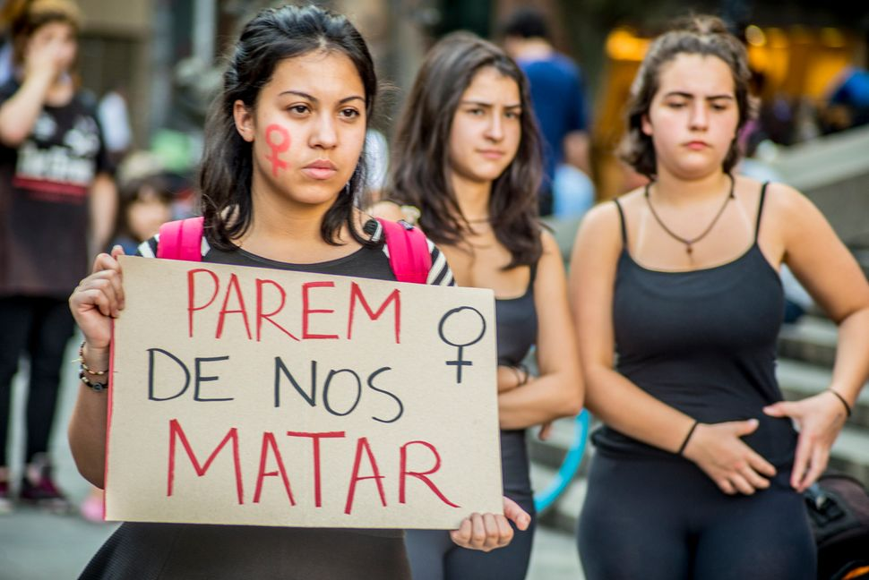 "Women in Sao Paulo, Brazil protest with a sign that says, ""Stop Killing Us."""