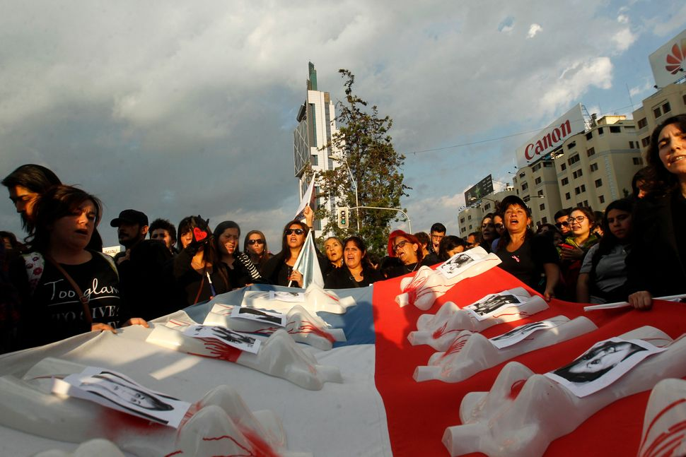 People hold a flag with missing and murdered women's photos during a march in Santiago, Chile on October 19.