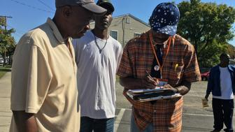 Muhammad Assaddique AbdulRahman helps a man fill out his voter registration in the Richmond neighborhood of Blackwell on Oct 17