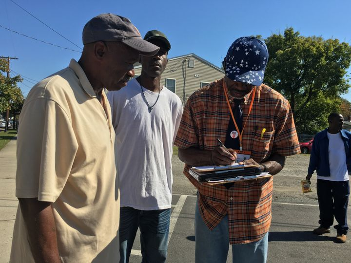 Muhammad As-saddique Abdul-Rahman (right) helps Richard Simms, 57, and Keith Butts, 53, fill out their voter registratio