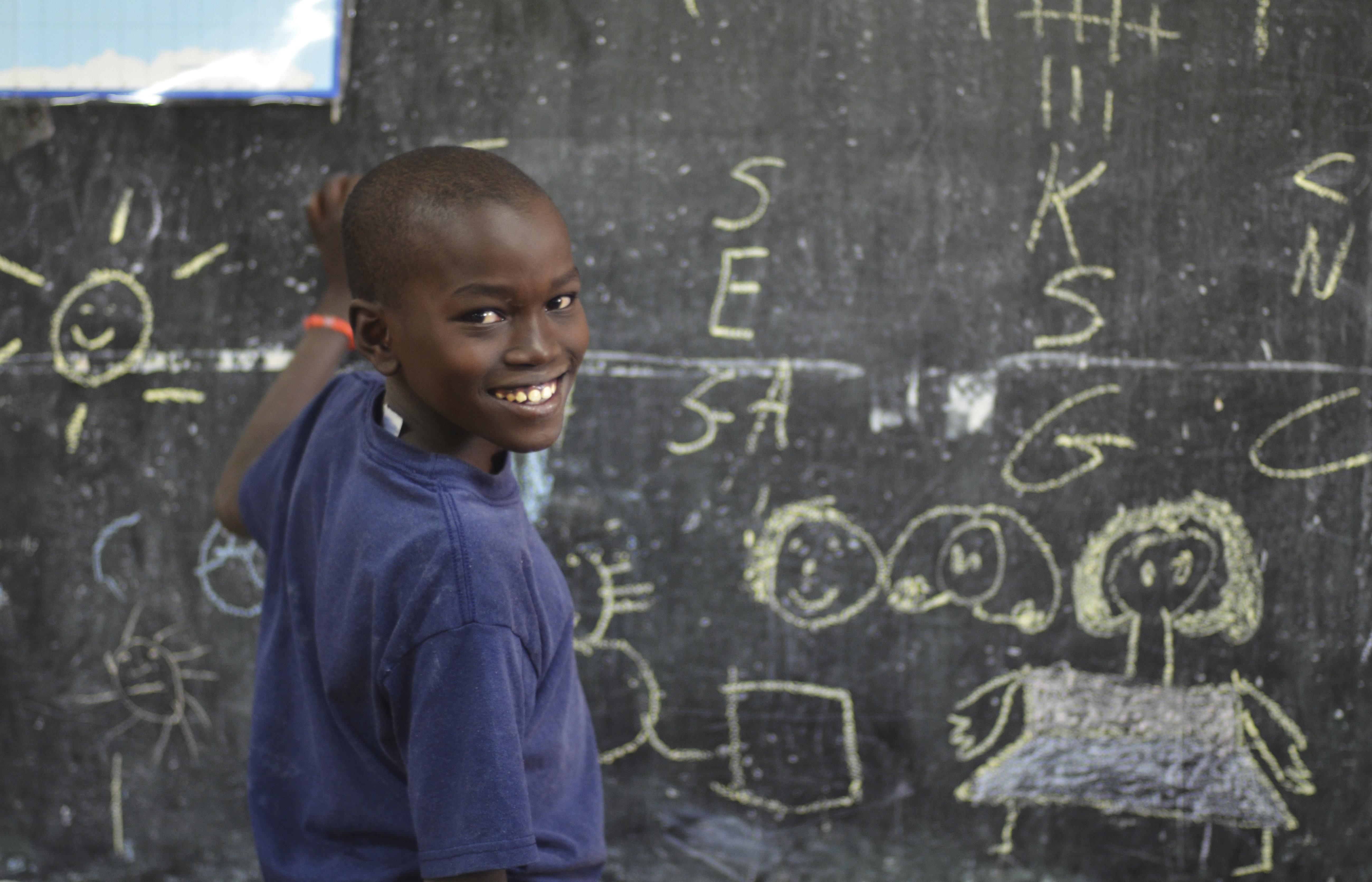 Kenya, Nairobi, little boy writing with chalk on blackboard