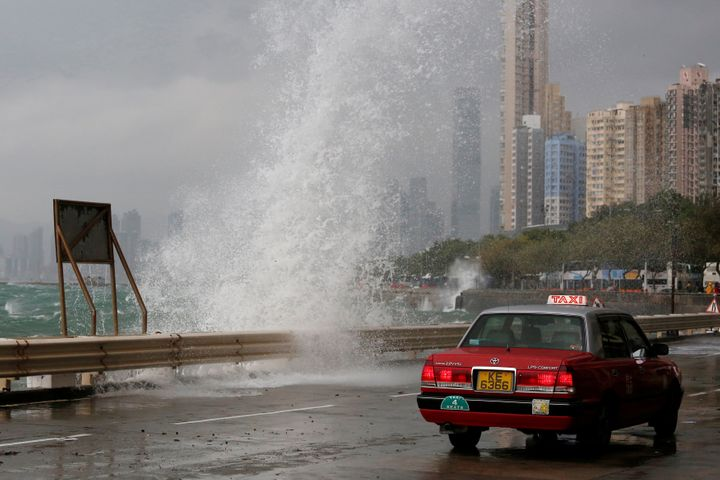 A taxi drives past a big wave on a waterfront as Typhoon Haima approaches in Hong Kong.