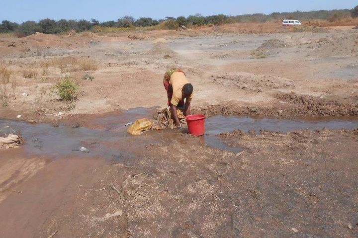 A woman washes canvas to cover minerals outside an artisanal mine in DRC. New report from Women's International League for Pe