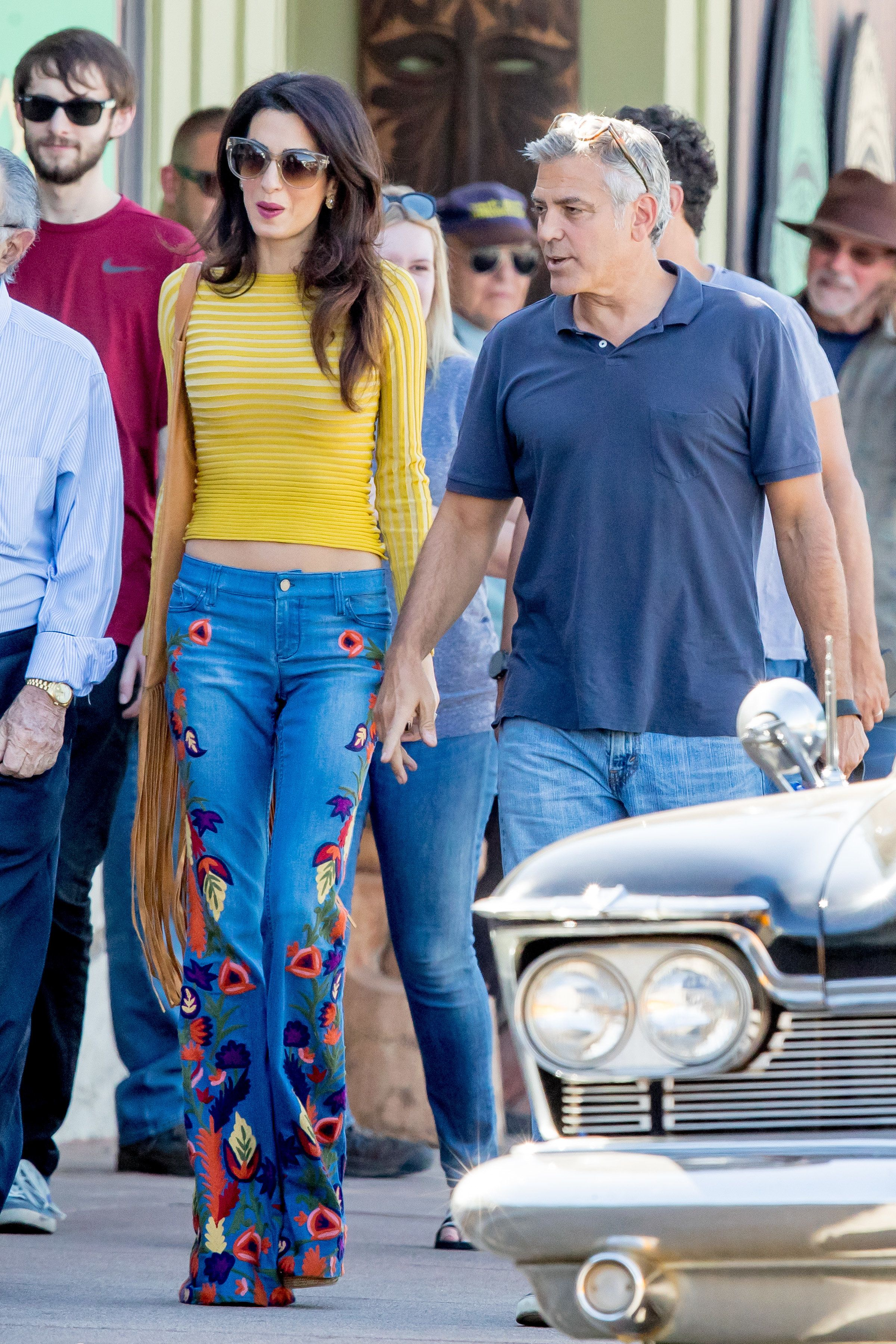 George Clooney and wife Amal Cooney seen holding hands as they walked their dog on the set of Suburbicon in Los Angeles, CA