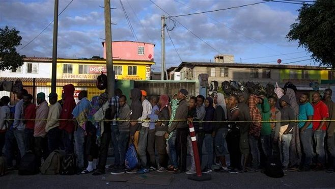 Haitian and African migrants seeking asylum in the U.S. line up outside a migration office in Tijuana, Mexico. Haitians are f