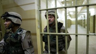 U.S.soldiers guard cells inside the prison of Abu Ghraib, outside Baghdad, Iraq, Wednesday, May 5, 2004. (AP Photo/Anja Niedringhaus)