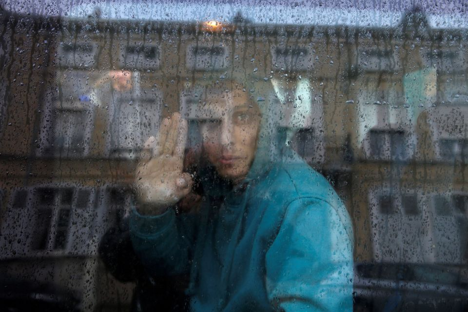 An adolescent Afghan migrant waves from a van as he departs with six others from anemergency shelter...