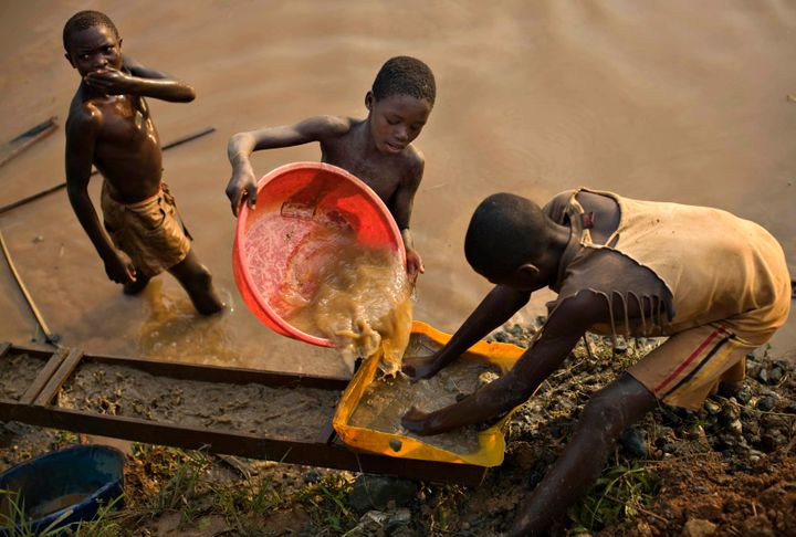 Boys pan for gold on a riverside at Iga Barriere in eastern Congo.