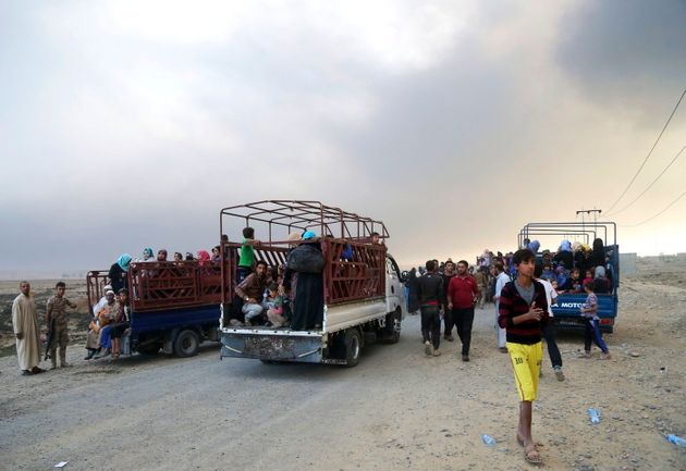 Smoke rises as people flee their homes during clashes between Iraqi security forces and members of the...