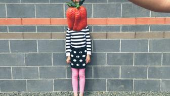 Portrait of child with large strawberry being held in front of face
