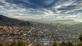 View from Panecillo Hill at sunrise towards La Basilica Del Voto Nacional across the city of Quito, Ecuador