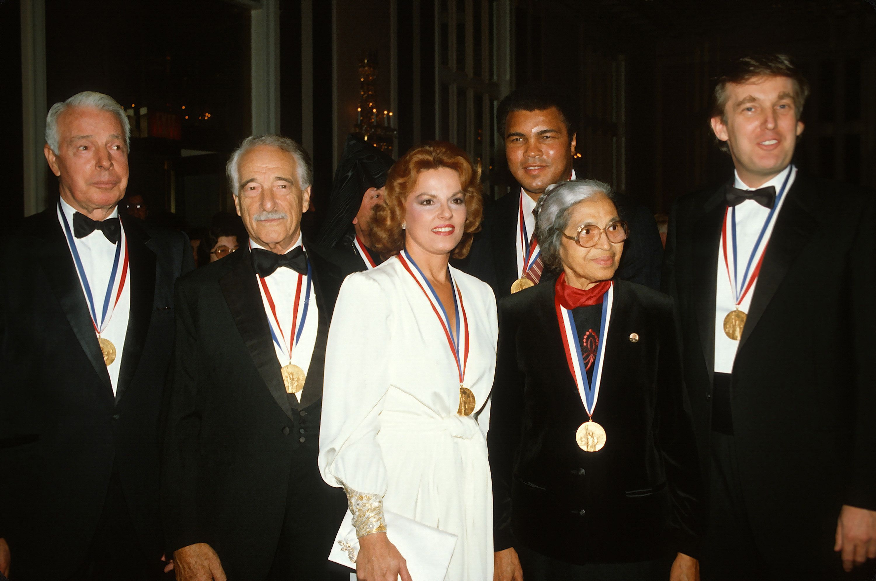 (Left to Right) Joe DiMaggio, Victor Borge, Anita Bryant, Muhammad Ali, Rosa Parks, and Donald Trump pose for a photograph af