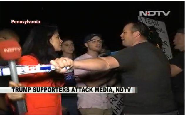 A Donald Trump supporter outside a campaign rally in Newtown, Pennsylvania, bats away NDTV reporter Namrata...