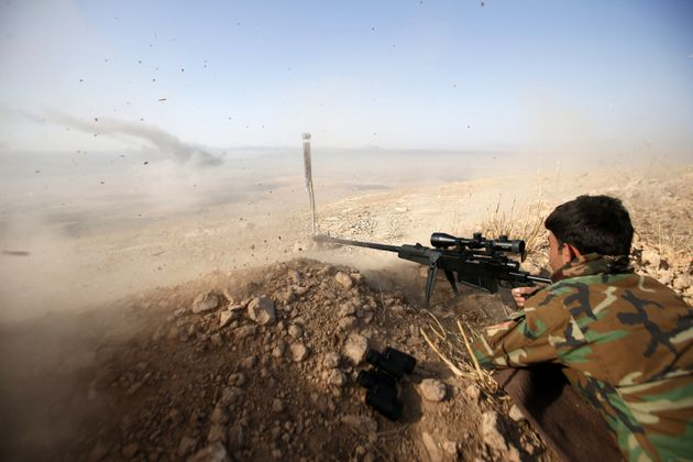 A Kurdish peshmerga fighter shoots during an operation to attack Islamic State militants in the town...