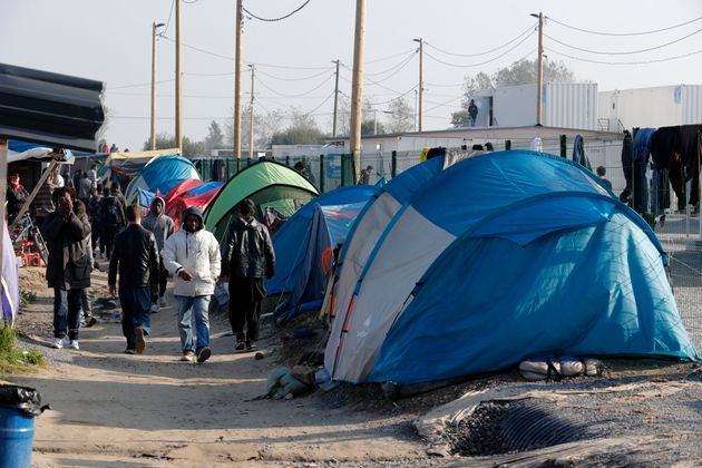 Migrants walk in an alley near tents and makeshift shelters on the eve of the evacuation and dismantlement...