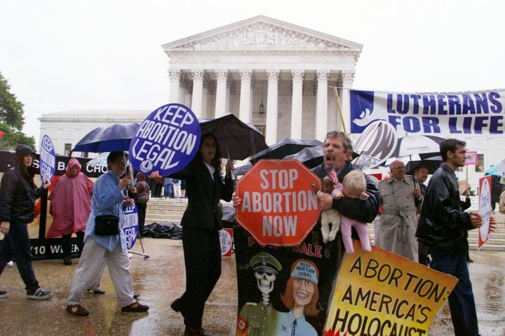Pro-choice and anti-abortion activists demonstrate in front of the Supreme Court building as arguments on Nebraska's partial