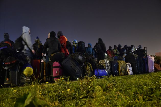 People queue for transportation with their belongings at the