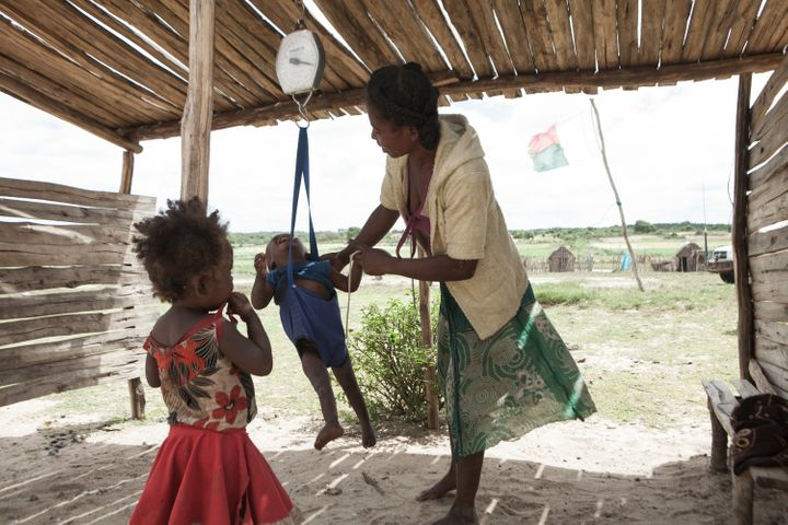 Awoman checks the weight of her baby at ahealth center insouthern Madagascar on March 4, 2015.