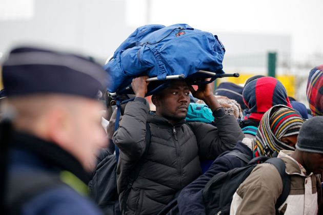 French police stand near as migrants with their belongings queue in Calais on