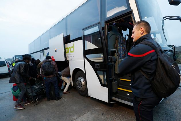 Migrants place their belongings on a bus at the start of their evacuation and transfer in Calais on