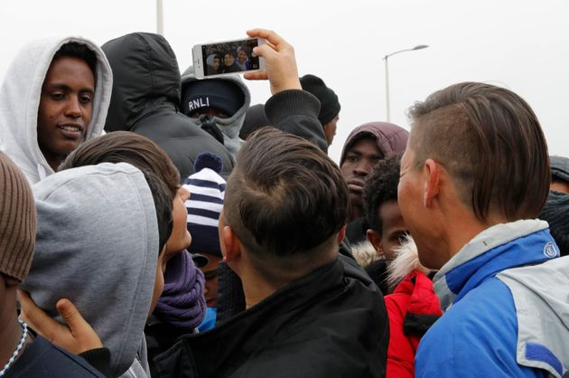Migrants queue at the start of the evacuation of 'The Jungle' camp in Calais, France on