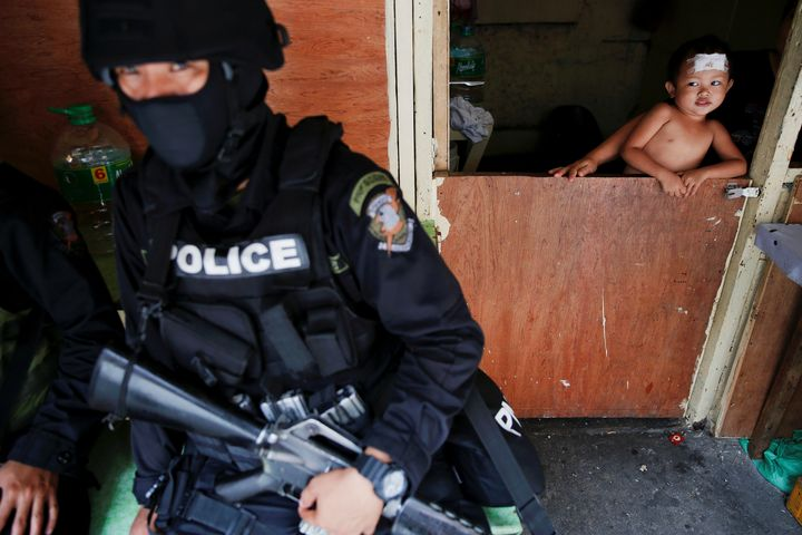 A baby looks at an armed member of a police SWAT team during a drug raid, in Manila, Philippines, October 7, 2016.