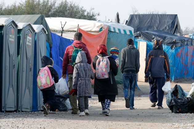 A migrant family walks with their belongings on Sunday, the day before the evacuation of 'The Jungle'...
