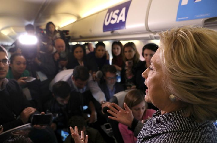 Reporters ask Hillary Clinton questions aboard her campaign plane.