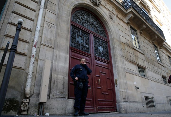 A police officer stands guard at the entrance of a luxury residence on the Rue Tronchet in central Paris, France, Oct. 3, 201