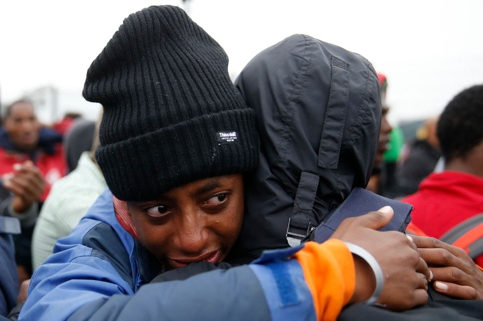 """An Ethiopian migrant, member of the Oromo community, cries as he leaves the """"Jungle."""""""