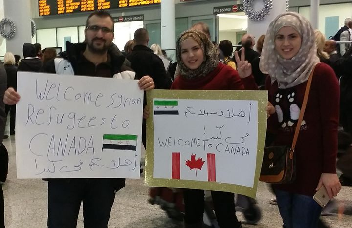 At Toronto's international airport, people gather to welcome new arrivals from Syria on Dec. 9, 2015.