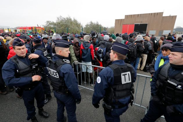 Police stand near as migrants with their belongings queue near barriers at the start of their