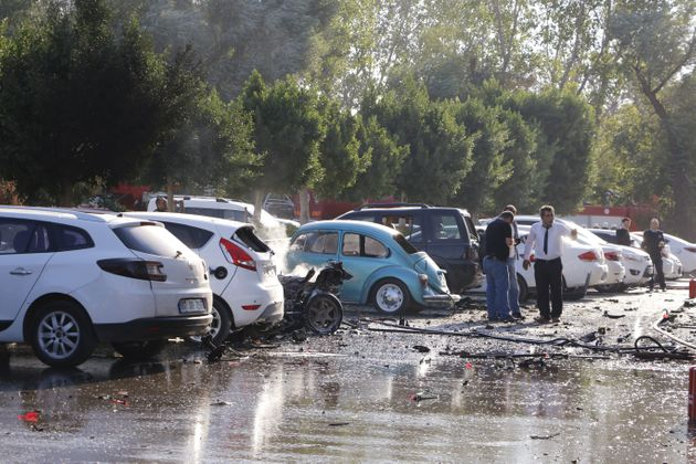 People stand by damaged cars near the site of an explosion in Antalya on