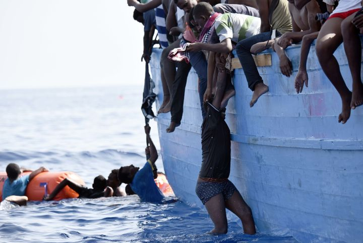 A migrant hangs from a boat as they wait to be rescued as they drift in the Mediterranean Sea, some 12 nautical miles north o