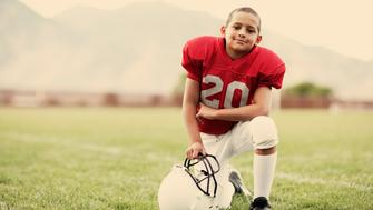 A young American boy loves being on the football field.