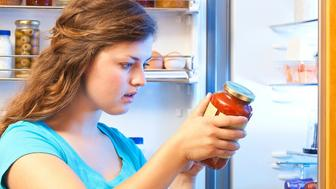 A Caucasian young woman standing in front of her kitchen's open refrigerator door, reading a glass jar canned food label. The female is intensely studying the packaged food list of ingredients, health criteria, and nutrition facts, keen to make smart choices for nutrition, organic diet, and calorie consumption. Horizontal view.