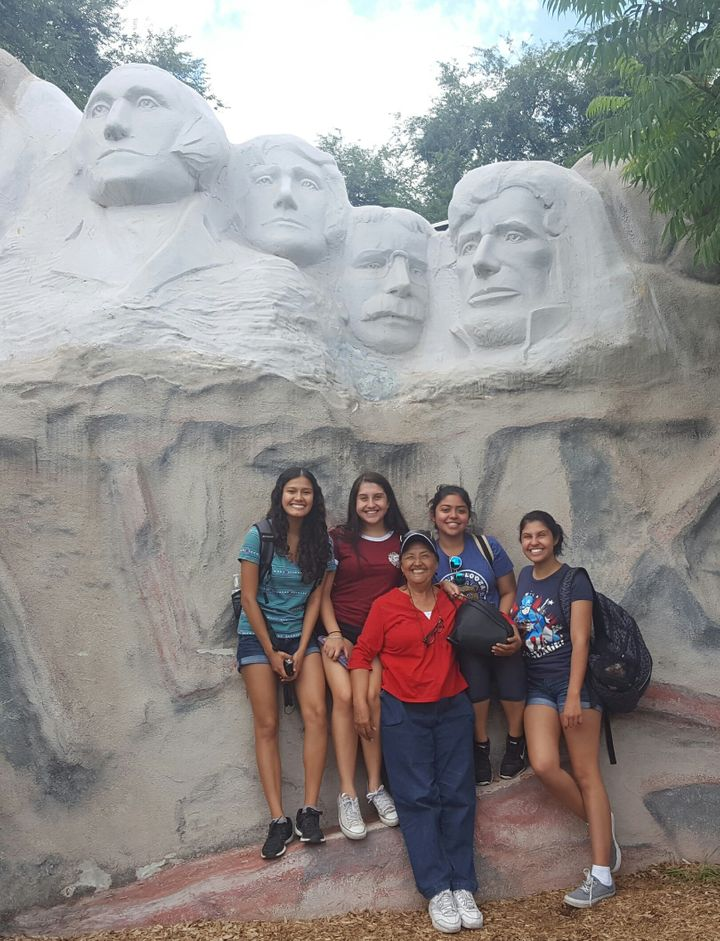 Cassandra Ruiz (L) with her family in South Dakota, posing with a miniature Mt. Rushmore.