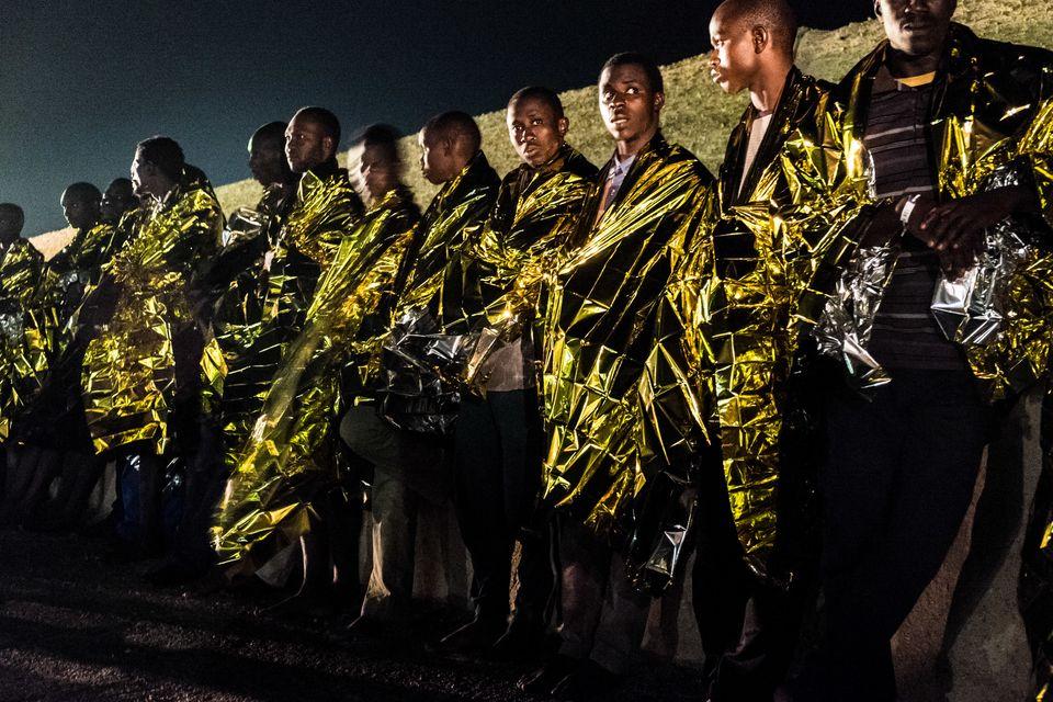 Migrants rescued by the Italian Coast Guard disembark onto