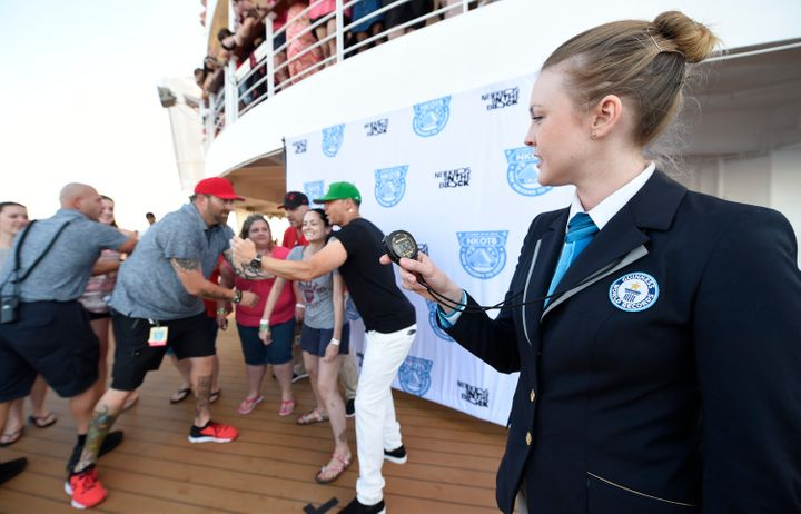 Guinness Worlds Record adjudicator Sarah Casson watches as Donnie Wahlberg poses for a record 122 selfies in 3 minutes.