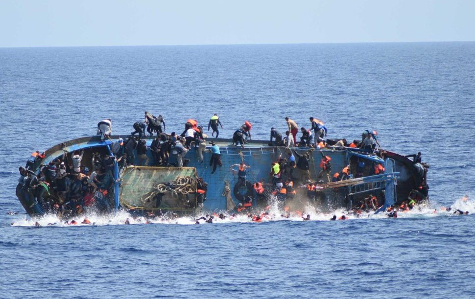 A migrant boat capsizes in the Sicilian Strait, between Libya and Italy, on May 25.