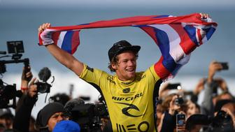 Hawaian surfer John John Florence waves his country's flag after securing the World Surf League World Title at Supertubos beach near Peniche, central Portugal, on October 25, 2016. / AFP / FRANCISCO LEONG        (Photo credit should read FRANCISCO LEONG/AFP/Getty Images)